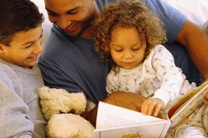 Father reading story to daughter and son